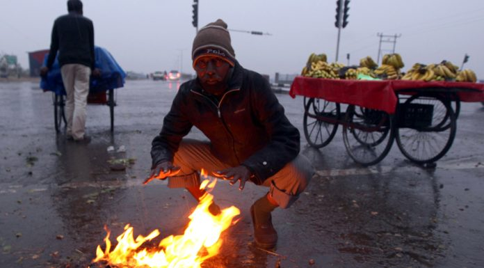 A vegetable vendor warms himself around fire in Jammu on Sunday. — Excelsior/Rakesh