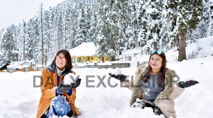 Tourists play with snow after fresh snowfall in Gulmarg. -Excelsior/Aabid Nabi