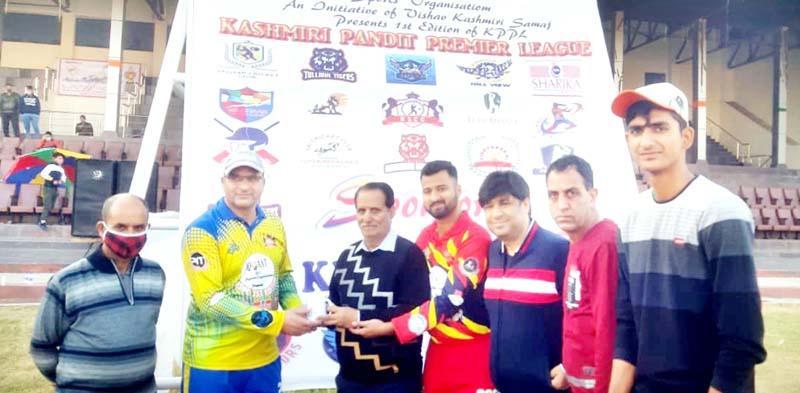 Working Committee Member JKCA Kanya Lal Koul presenting trophy to man of the match winner at MA Stadium Jammu.