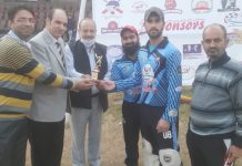 Dignitaries presenting trophy to a player during KPPL match at MA Stadium Jammu.