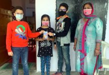 Eleven-year-old twins, Aryan and Rohan Gupta donating a mobile phone to a girl student at a Government School in Jammu.