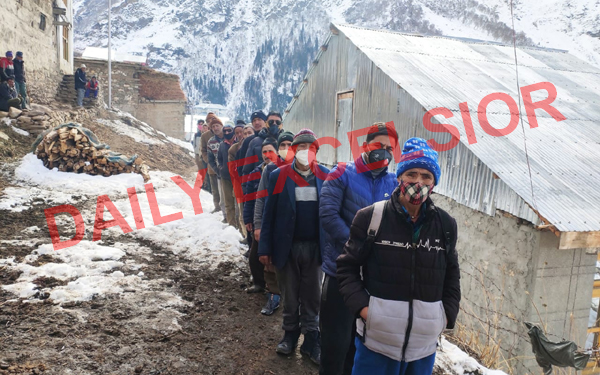 People in queue outside a polling station in snow covered Kabban area of Paddar. —Excelsior/Tilak Raj