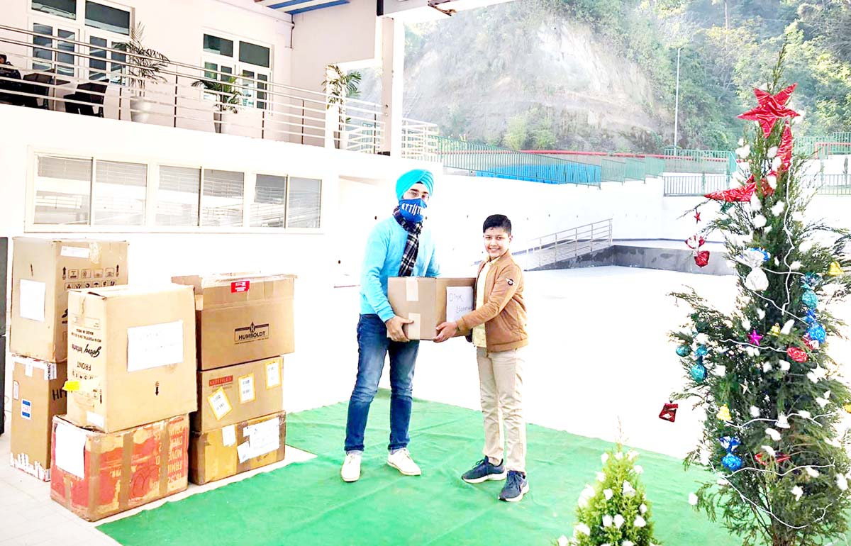A boy donating box containing warm clothes to a member of NGO 'The Sara' during a function at Jammu on Friday.