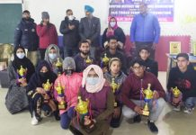 Winning players posing for a group photograph with their trophies at Shopian.