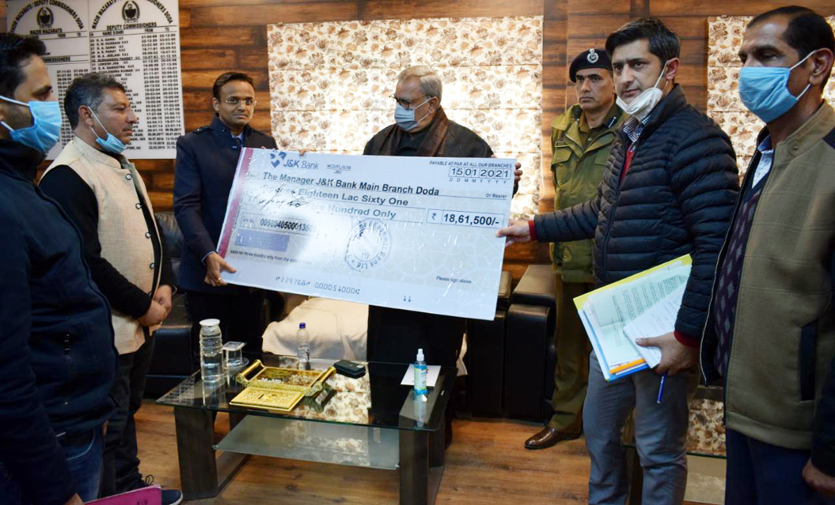 Advisor Farooq Khan presenting cheque for beneficiaries on Friday.