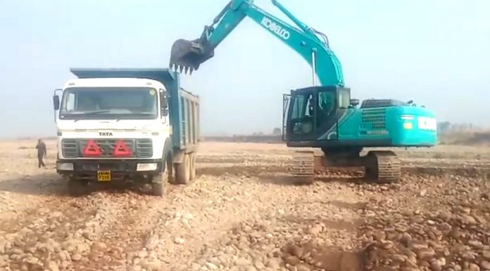 An excavator digging near Ujh bridge and loading Tipper at Kotpunnu in Kathua. -Excelsior/Pardeep