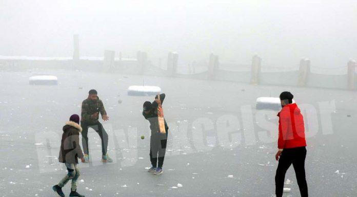 Boys playing cricket on frozen Dal lake in Srinagar on Thursday. -Excelsior/Shakeel