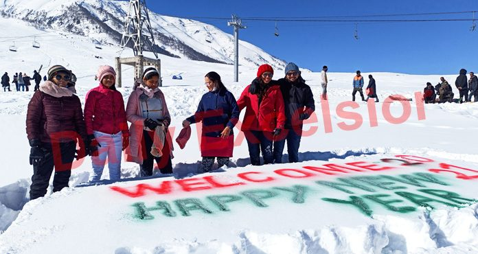 Tourists writing New Year greetings on snow in Gulmarg. -Excelsior/Aabid Nabi