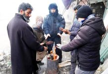 People warm themselves near bonfire in Srinagar. -Excelsior/ Shakeel