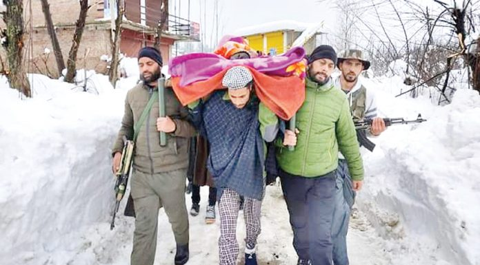 Cops and locals shift pregnant woman to hospital at Keller in Shopian district on Wednesday. —Excelsior/Younis Khaliq