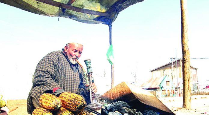 An old man selling corn on a cold morning near Narmal area on Srinagar-Muzaffarabad road. -Excelsior/Aabid Nabi