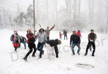 Tourists enjoying snowfall in Srinagar on Saturday. -Excelsior/ Shakeel