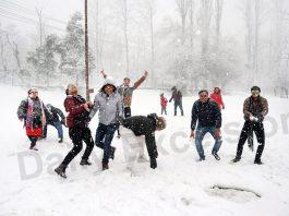 Tourists enjoying snowfall in Srinagar on Saturday. -Excelsior/ Shakeel