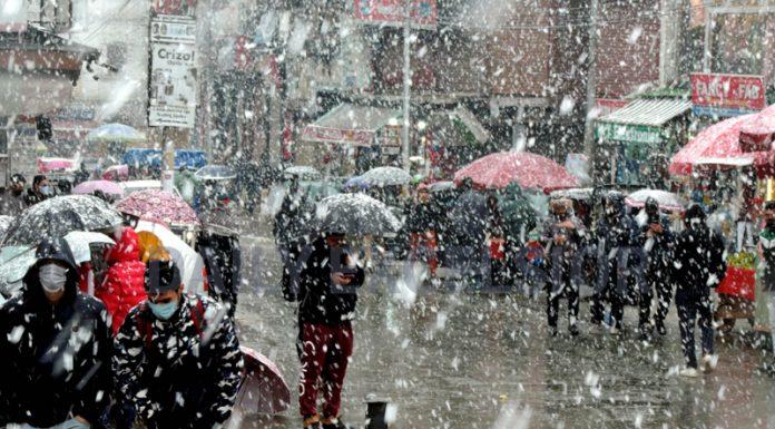 People cover themselves under umbrellas as Srinagar experiences fresh snowfall on Monday. (UNI)
