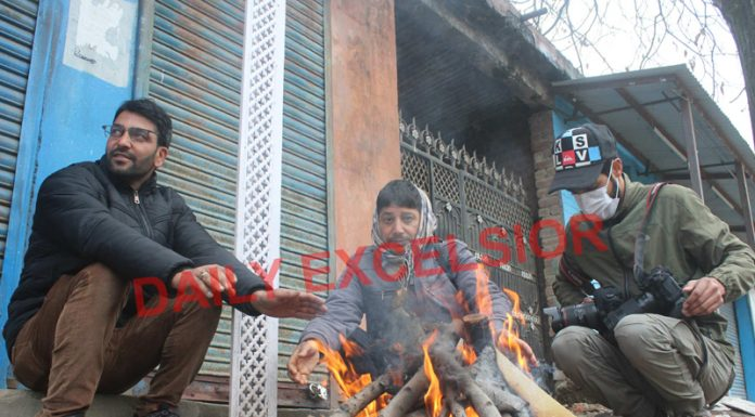A group of men warming their hands amid bone chilling cold in South Kashmir's Pulwama district on Sunday. —Excelsior/Younis Khaliq