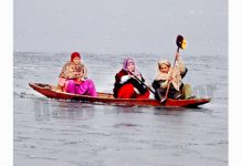Women breaking frozen ice with oars at Dal lake in Srinagar. -Excelsior/Shakeel