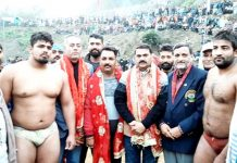 Wrestlers and dignitaries posing for a group photograph at Reasi.