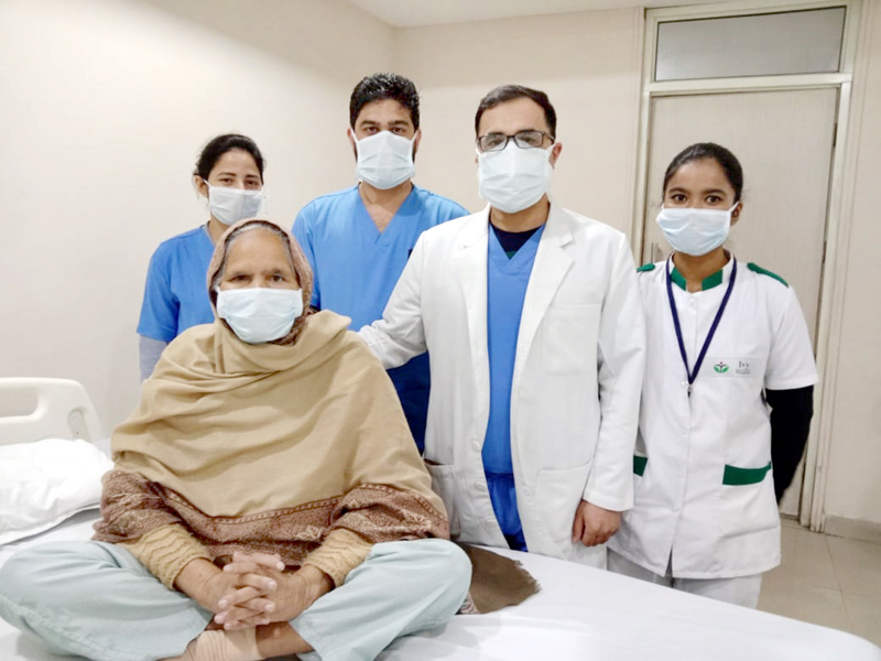 Patient and doctors posing for group photograph.
