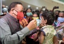 Union Health Minister Harsh Vardhan helps a child wear a face mask during his visit to review the dry run for administering COVID-19 vaccine at Tamil Nadu Government Multi Super Speciality Hospital, in Chennai.