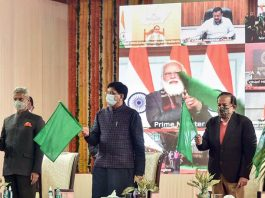 Union Railway Minister Piyush Goyal, External Affairs Minister S Jaishankar and Health Minister Harsh Vardhan wave green flags as Prime Minister Narendra Modi virtually flags off eight trains connecting Statue of Unity in Kevadia, Gujarat with different regions of the country, at Nizamuddin Railway Station in New Delhi on Sunday.