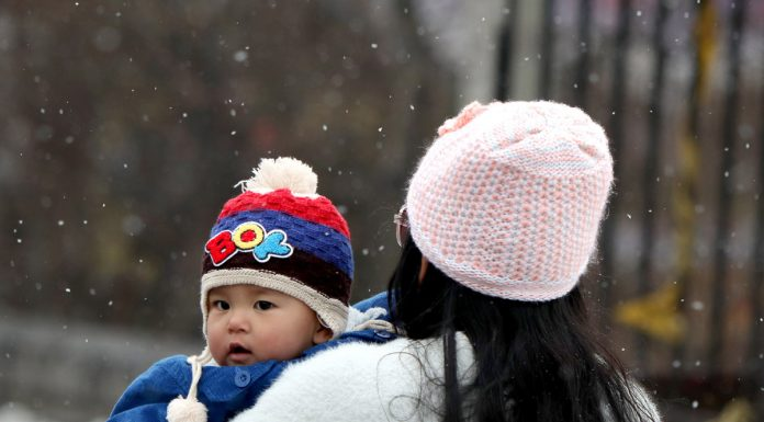 A mother carries her child amid fresh snowfall in Srinagar. -Excelsior/Shakeel