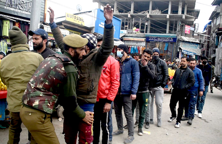 Security forces conduct searches of pedestrians in Lal Chowk area of Srinagar on Monday. —Excelsior/Shakeel