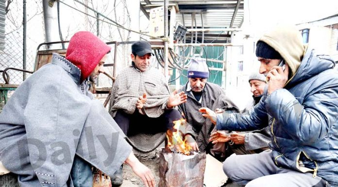 People warm themselves on a cold winter day in Srinagar. -Excelsior/Shakeel