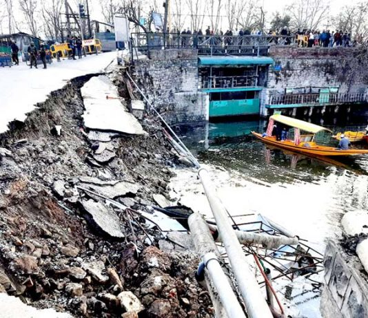 Portion of road caves in near Dalgate in Srinagar on Wednesday. -Excelsior/Shakeel