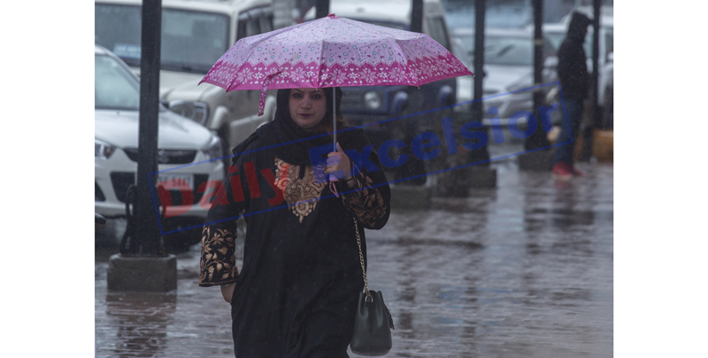A woman holding umbrella during a rain in Srinagar on Monday. — Excelsior/Shakeel