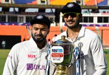 Rishabh Pant, left, looks on as teammate Axar Patel holds the winners trophy after winning fourth cricket test match against England at Narendra Modi Stadium in Ahmedabad on Saturday. (UNI)
