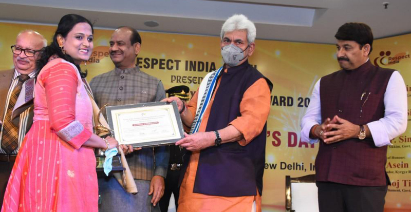Lt Governor Manoj Sinha giving away Pride of Nation Excellence Award-2021 to a woman achiever in Delhi.