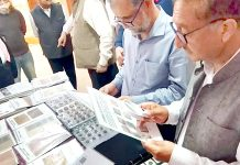Academicians and cultural activists minutely examining rare stamps and coins put on display in an exhibition in Jammu.