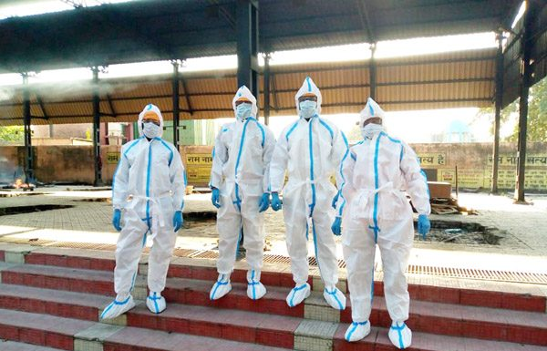 Relatives of COVID infected person wearing PPE kits at the cremation site after performing last rites of the victim in Jammu on Sunday. (UNI)