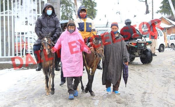 Tourists enjoy snowfall in Gulmarg on Saturday. —Excelsior/Aabid Nabi