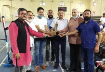 Former Minister Sham Lal Sharma and other dignitaries presenting trophy to a player during closing ceremony of Gold Badminton Championship at Akhnoor.