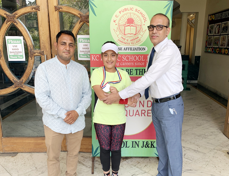 Principal of KC Public School Amarendra Mishra congratulating Shreemai Bhat for clinching Sliver medal in Soft Tennis Championship at Jammu.