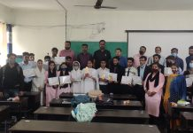 Winners of symposium displaying meritorious certificates along with dignitaries at Rajouri.
