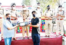 Police officials distributing sports equipments among players at Kathua on Monday.