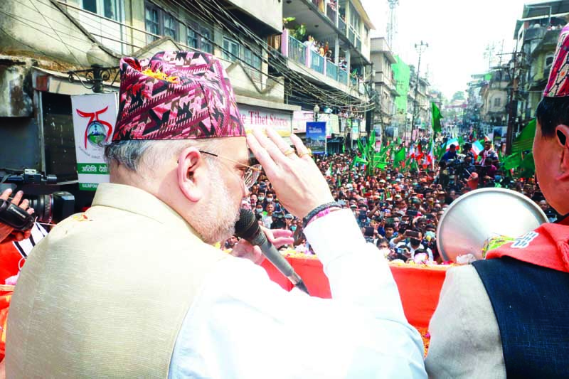 Union Home Minister Amit Shah greeting people during a road show in support of BJP candidates for West Bengal Assembly election at Kalimpong on Monday. (UNI)