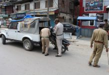 Police seizing a motorcycle for violating Corona curfew in Baramulla. — Excelsior/Aabid Nabi