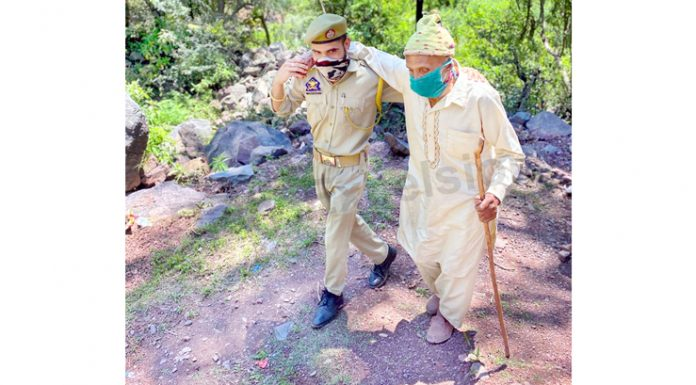 SPO Pankaj Kumar helps elderly villager to reach vaccination centre in Arnas area of Reasi on Saturday. -Excelsior/Romesh Mengi