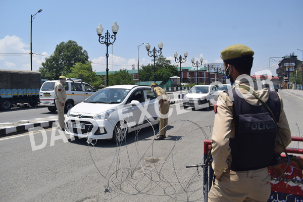 Cops check a car moving on Srinagar road during lockdown on Sunday. — Excelsior/Shakeel