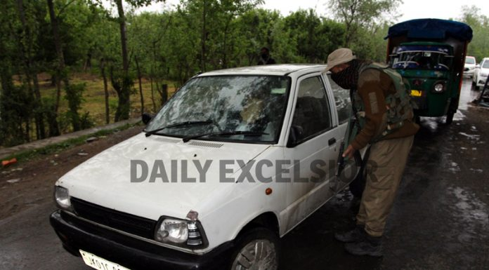 Security personnel check vehicles during encounter at Nathipora in Sopore on Tuesday. -Excelsior/Abid Nabi