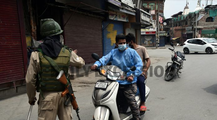 Cops check movement of vehicles during lockdown in Srinagar on Tuesday. -Excelsior/Shakeel