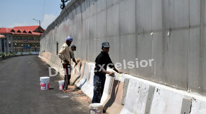 Ahead of Darbar Move, workers paint a wall of flyover in front of the Civil Secretariat road in Srinagar on Friday.— Excelsior/Shakeel