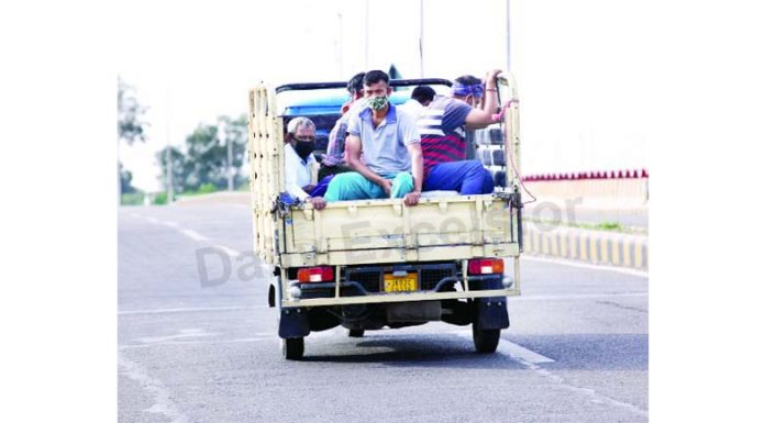People travel in a load carrier during lockdown at Bikram Chowk Jammu on Friday. —Excelsior/Rakesh