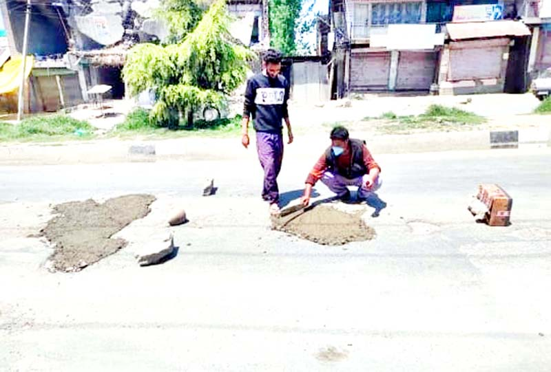 Locals in Narbal fill potholes of Srinagar-Gulmarg highway with concrete. -Excelsior/Photo