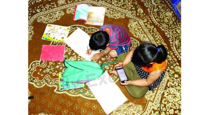Children attending routine online classes from home amid pandemic in Kashmir. —Excelsior/Aabid Nabi