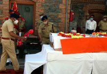 Senior police officers laying wreaths on the coffin of the two martyred cops who lost their lives in a militant attack at Sopore in North Kashmir. (UNI)
