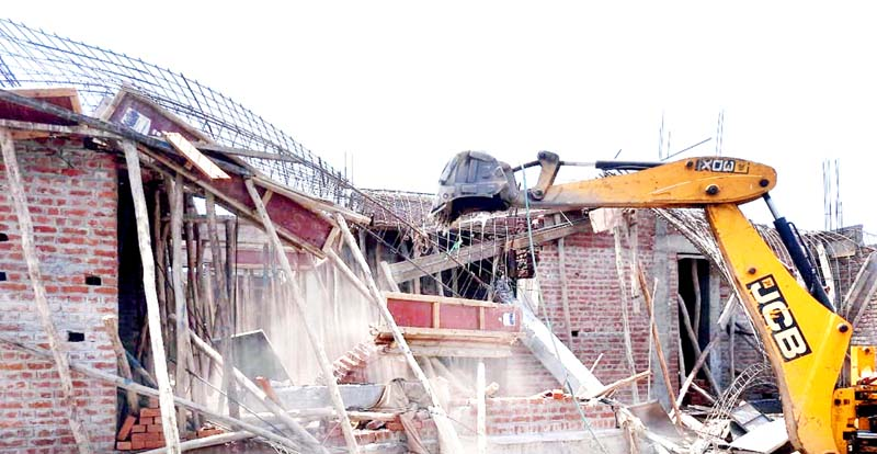 A JCB machine of JMC demolishing illegal structure at Sainik Colony, Jammu.